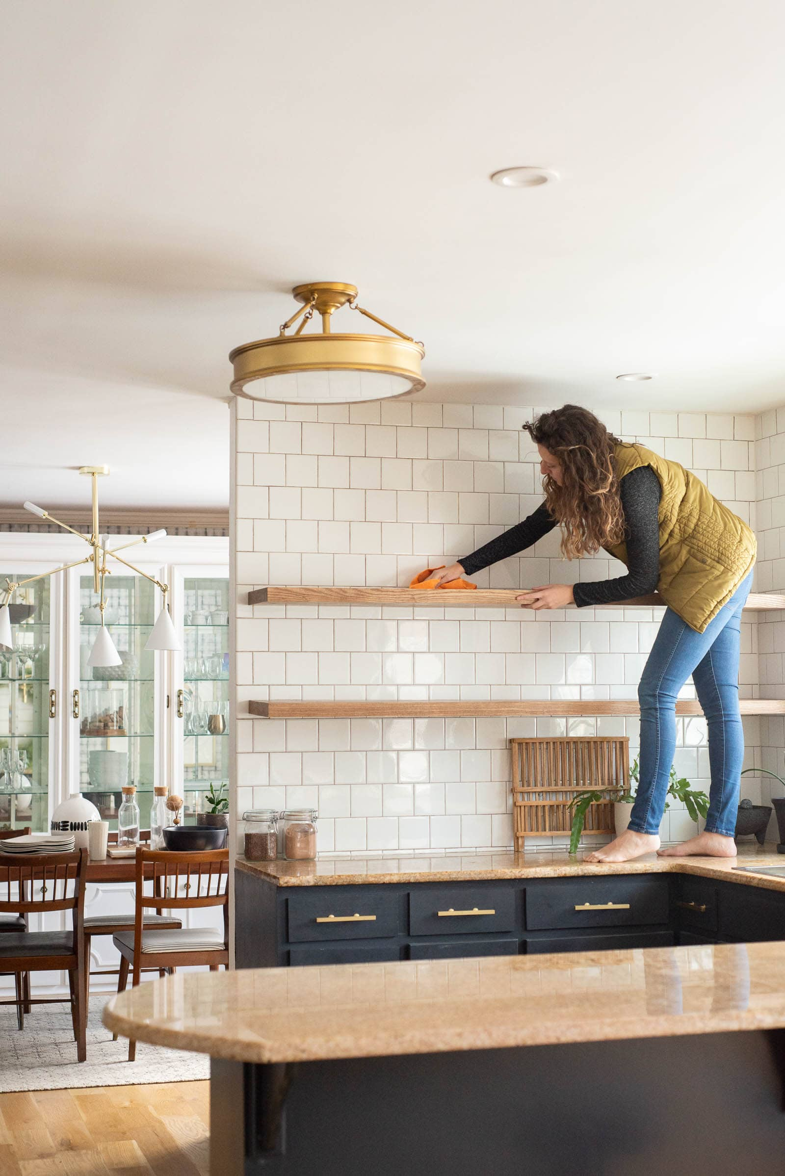 A woman on her counter cleaning her floating shelves