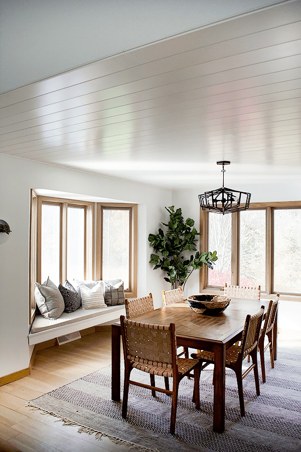 Dining room table with shiplap ceiling overhead.
