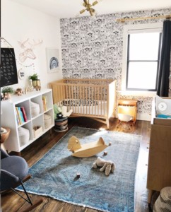 Nursery with wallpaper and a wooden rug