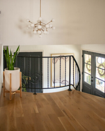 View of entryway with double front doors, stairs and art.