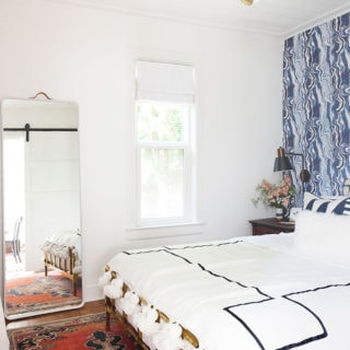White walls in bedroom with wallpaper and bed