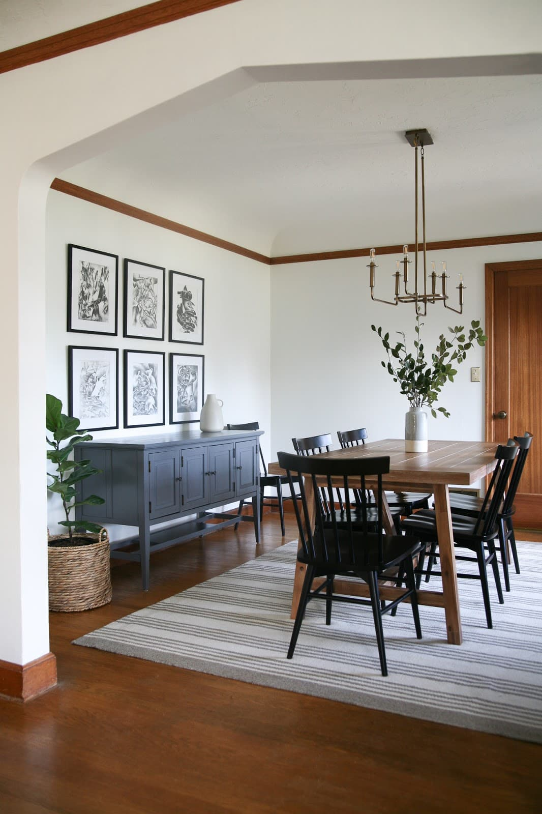 Dining room featuring a striped rug, black and white art and more,