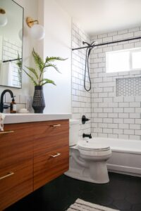 Midcentury inspired bathroom with oversized tile in shower and a wood cabinet