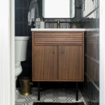 Modern powder bathroom with black tile and walnut vanity