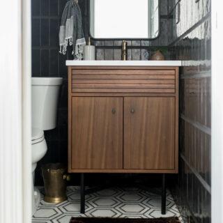 Modern powder bathroom with black tile and walnut vanity