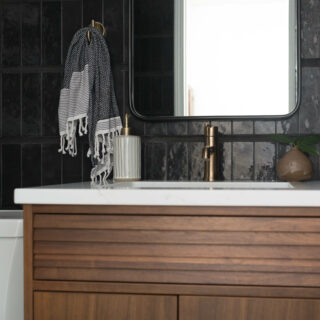 Walnut vanity in the powder bathroom with white quartz countertop and black wall tile