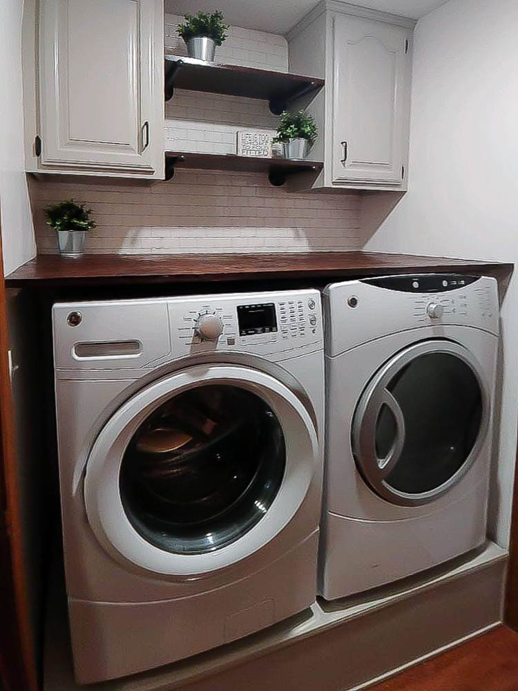 A newbie DIYers transforms the laundry room with peel and stick tile, DIY pedestal for washer and dryer and more.