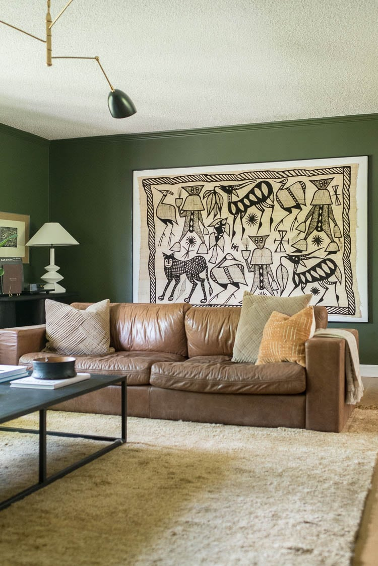 Upgrade a huge wall tapestry by mounting it on an oversized canvas. Show here is a big art piece in a DIY frame on a green wall in the living room.