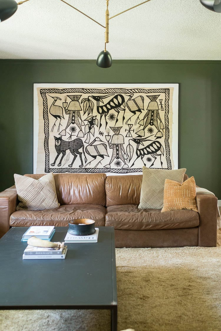green living room walls with Korhogo Cloth behind couch