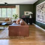 Forest Green Living Room Walls with leather couch, large art on wall and wood floors