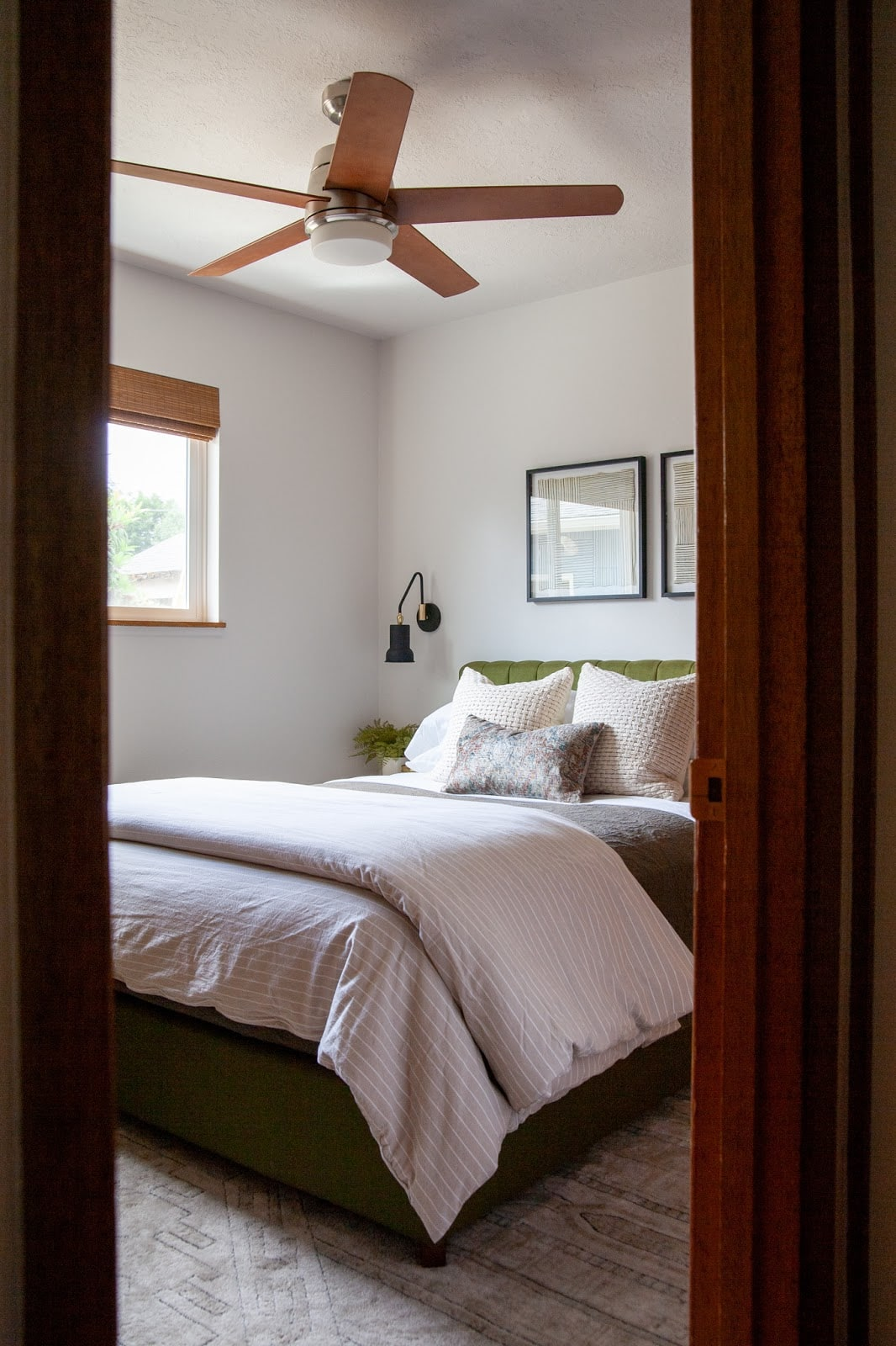 Guest room with green headboard, neutral bedding and fan
