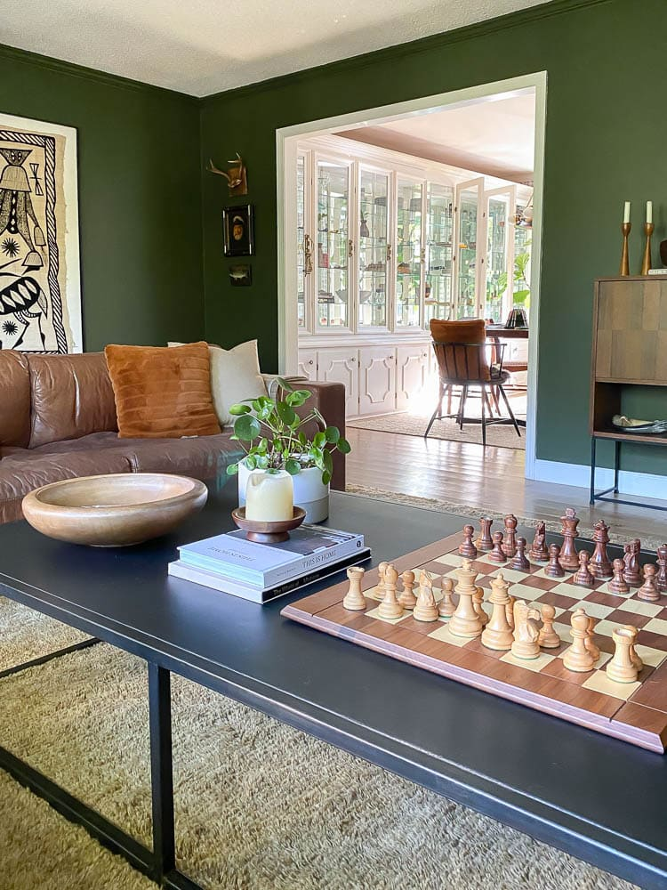 coffee table styled with chess board, plant and books in living room