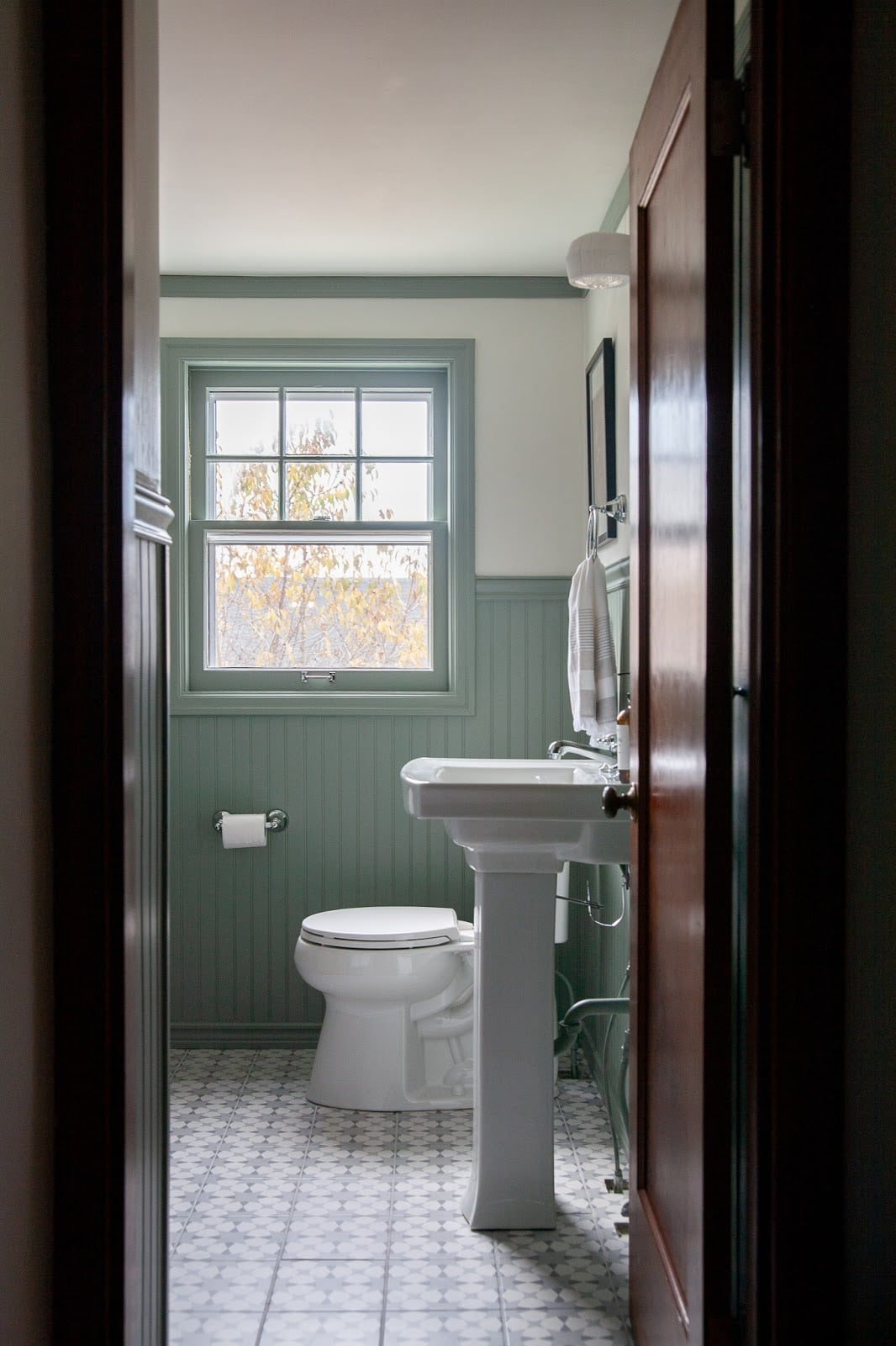 Modern traditional bathroom makeover featuring painted green bead board