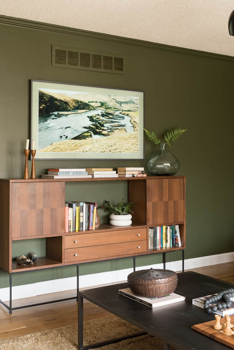 Green living room wall paint with mid century console filled with books