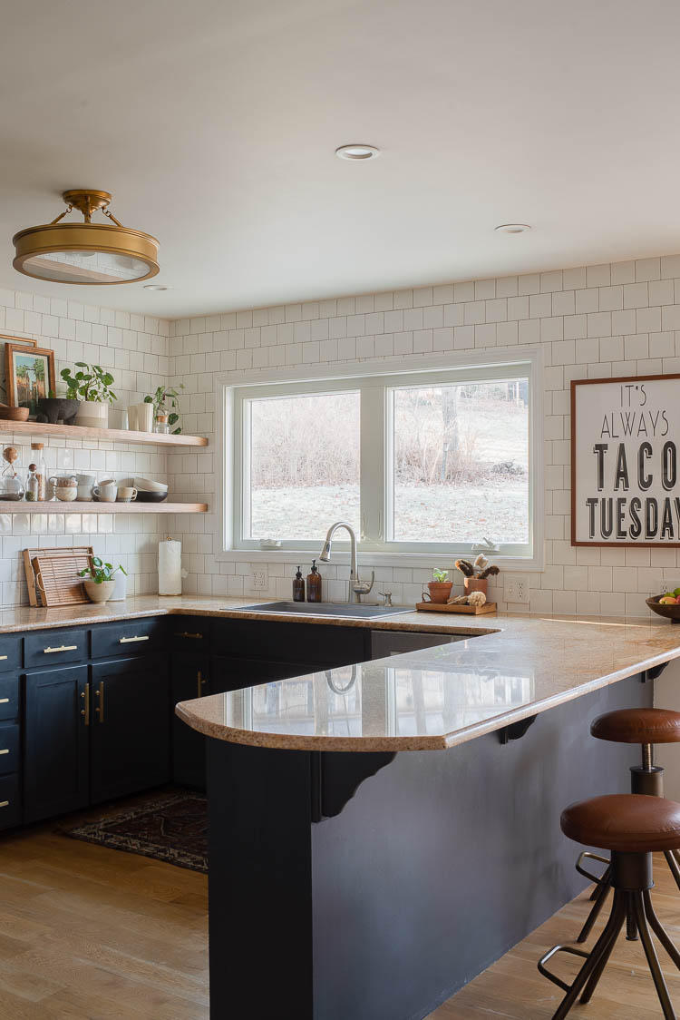 enlarge window in the kitchen showing window above kitchen sink with dark cabinets and subway tile