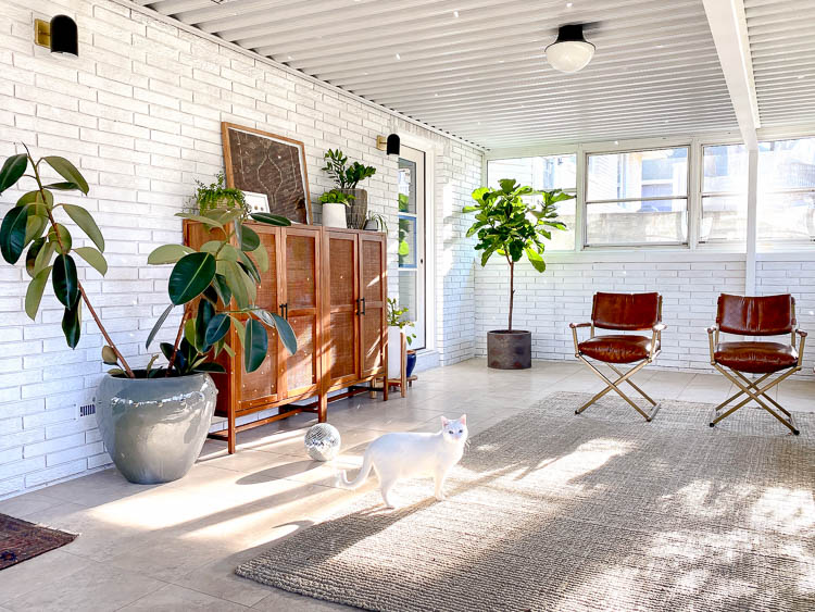 White brick in sunroom with plants and storage
