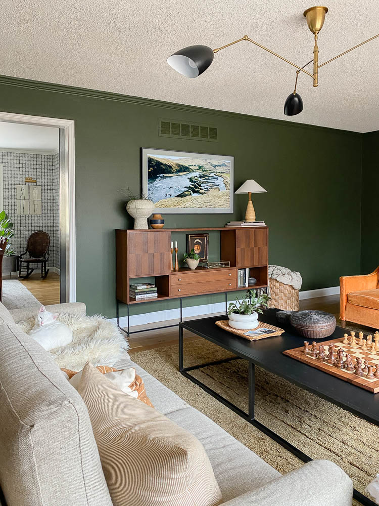 eclectic living room with a wood media console with shelving under the tv