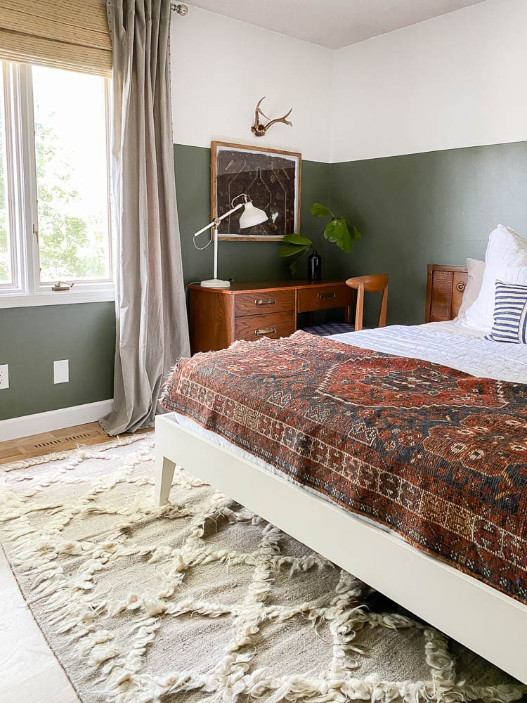 framed rug in bedroom with half green walls and bed