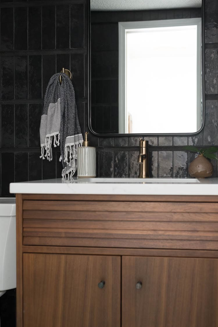 Use an epoxy adhesive to attach sink clips on a vanity top. Showing a closeup photo of walnut vanity with white quartz and brass fixtures.