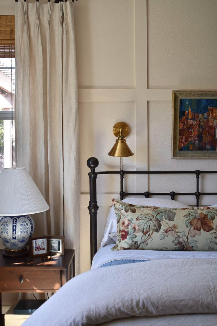 millwork in bedroom with iron bed and floral pillow