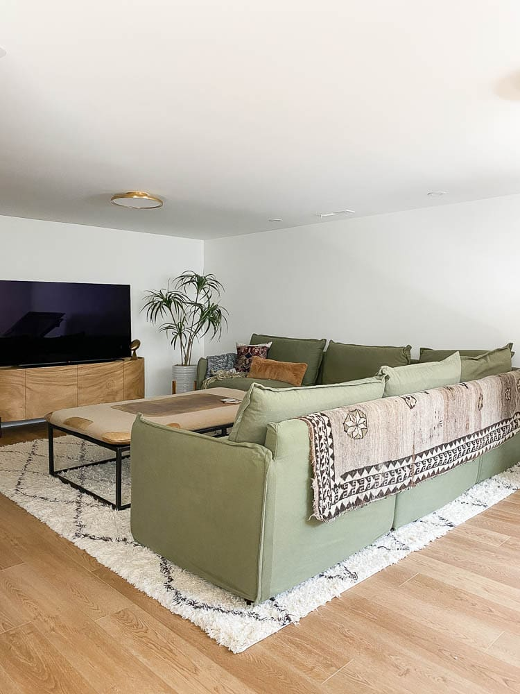 Sharing how to cut a rug to resize it. Showing a moroccan white rug underneath a sectional in the basement.