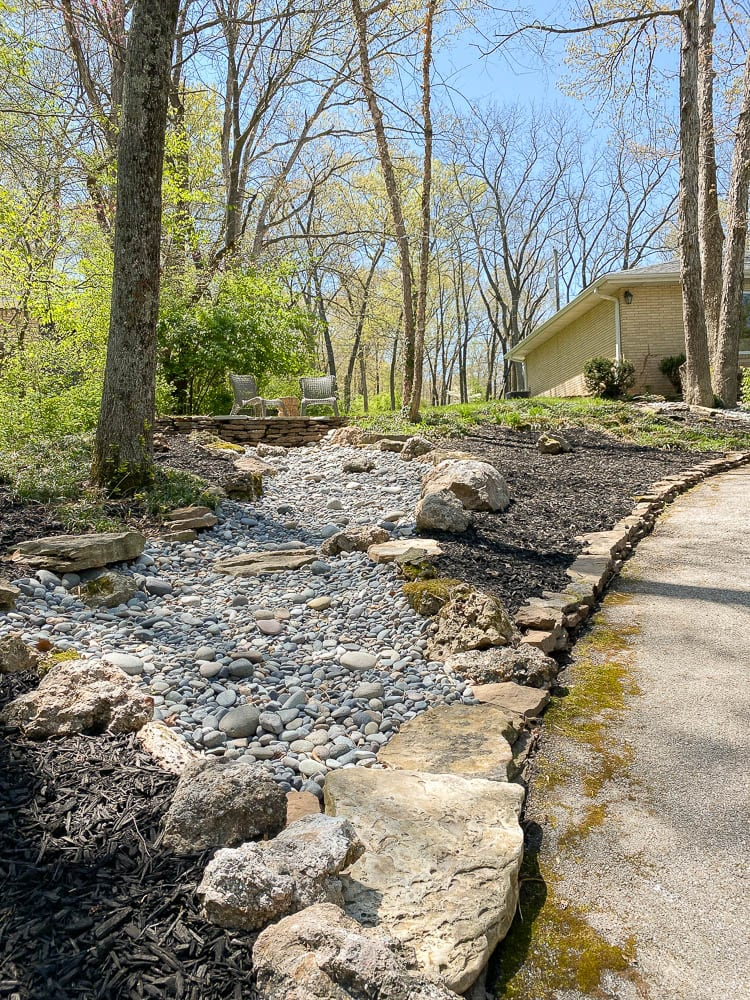 Rock landscaping showing a dry creek and how it ends at the driveway with a flagstone patio on top of the rock creek.
