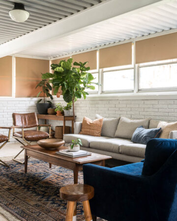 Four seasons sunroom with a vintage rug, grey couch and plants