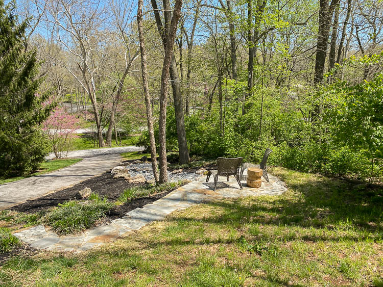 Side yard showing a flagstone patio and rock creek with rock landscaping around trees