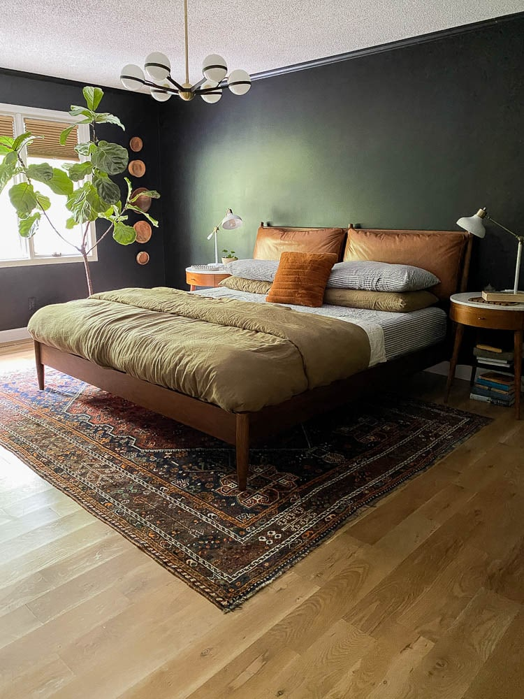 Linen sheets in the bedroom with a vintage rug and midcentury bed.