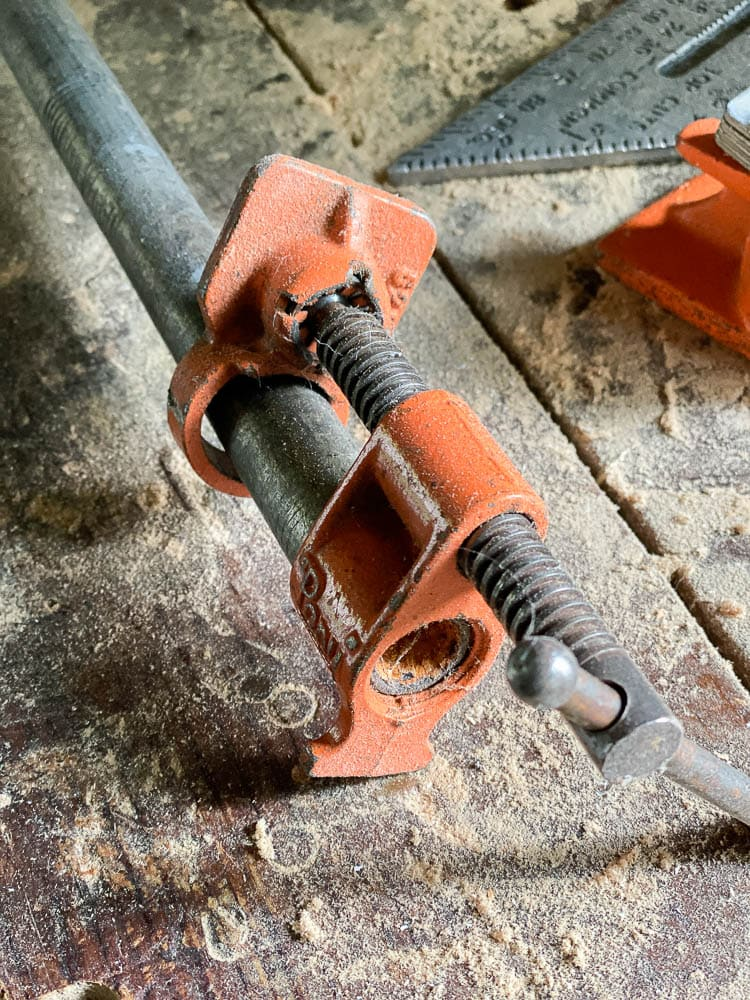 Closeup of pipe clamp on table with sawdust