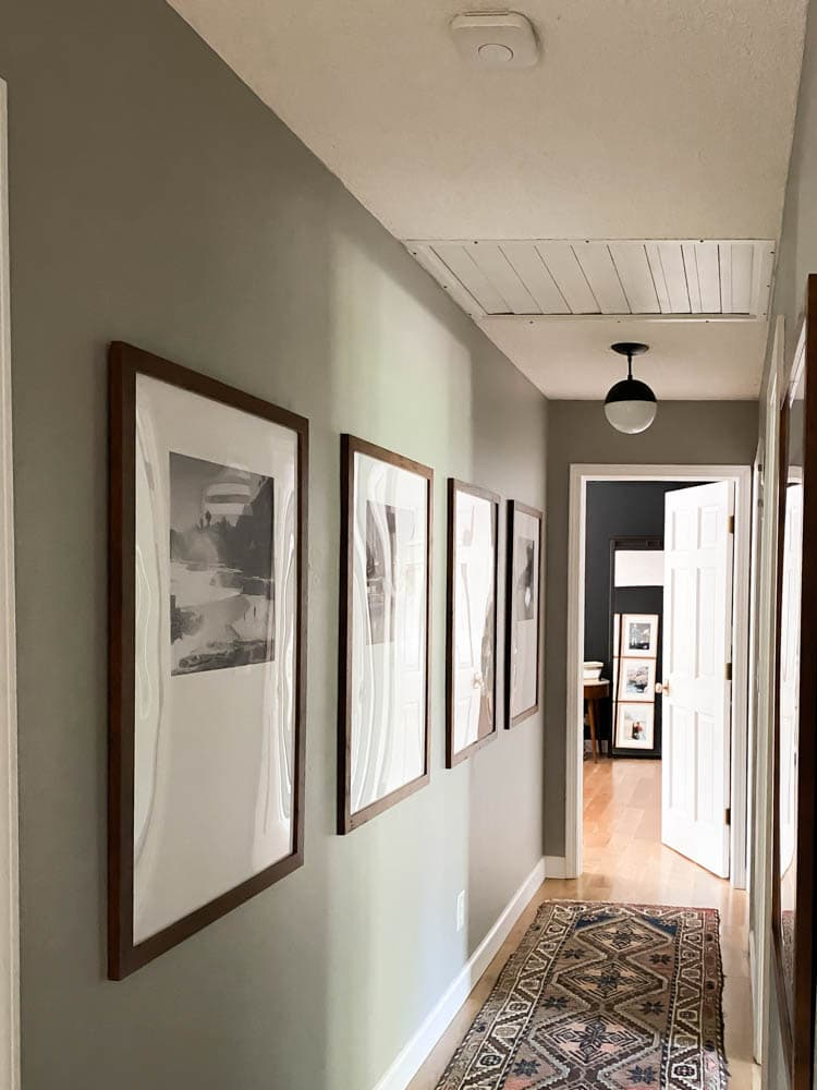 Nest Smoke Alarms are a great smart home automation tool. Showing the nest in a hallway with modern brown poster frames hanging.