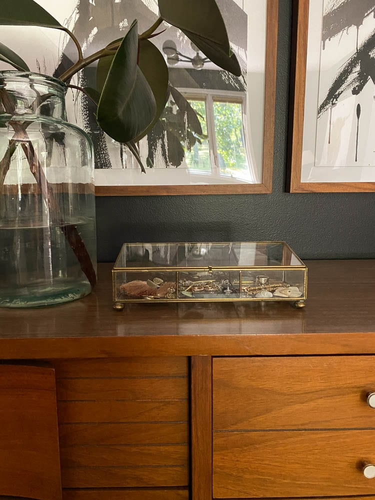 jewelry organizer ideas including a brass and glass small jewelry organizer sitting on a dresser in the bedroom