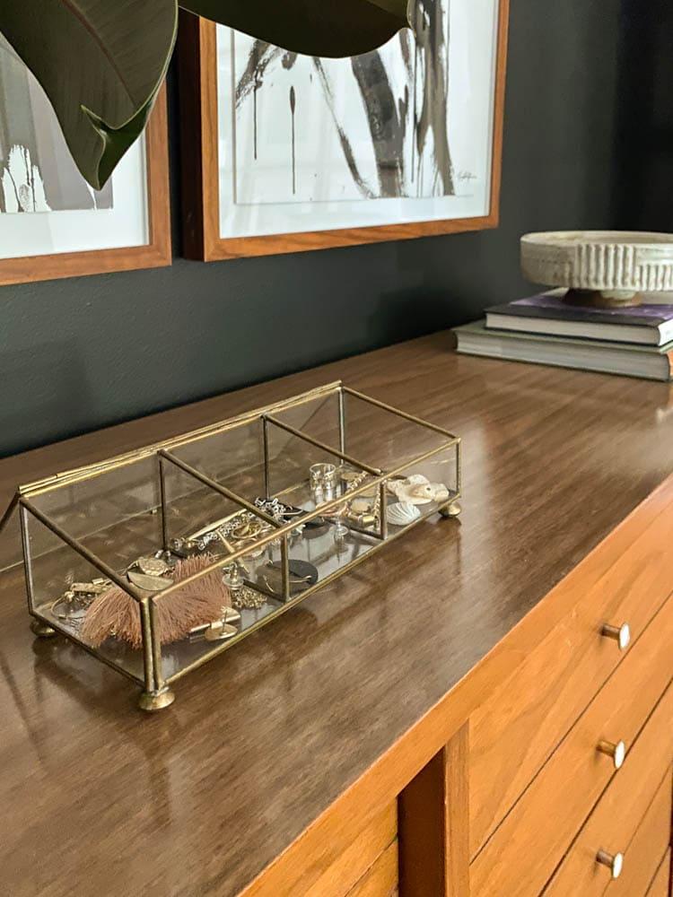 brass and glass jewelry organizer on midcentury dresser in bedroom